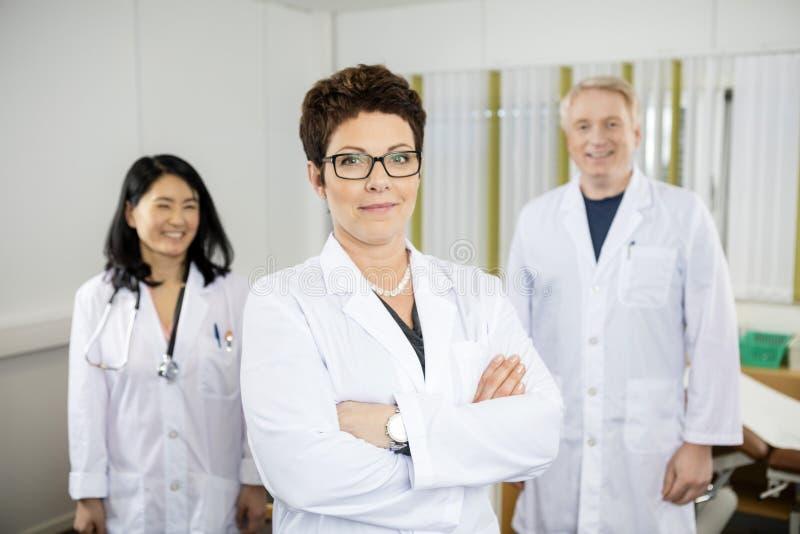 Doktor Standing Arms Crossed während Kollegen, die in der Klinik lächeln stockfotos