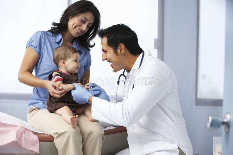 Doktor In Surgery Examining behandla som ett barn flickan arkivbild