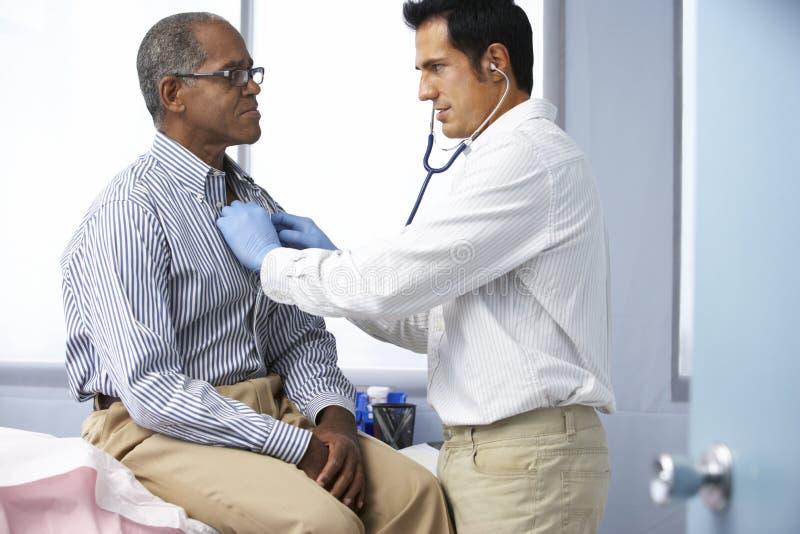 Doktor In Surgery Listening till manlig patients bröstkorg arkivfoto