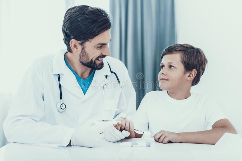 Doktor Taking Blood Sample från fingret för pojke` s arkivbild