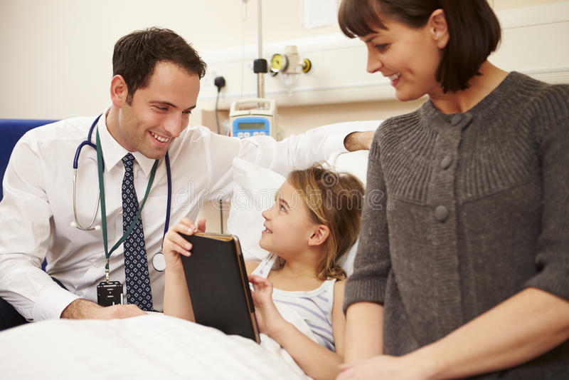 Doktor Talking To Mother och dotter i sjukhussäng fotografering för bildbyråer