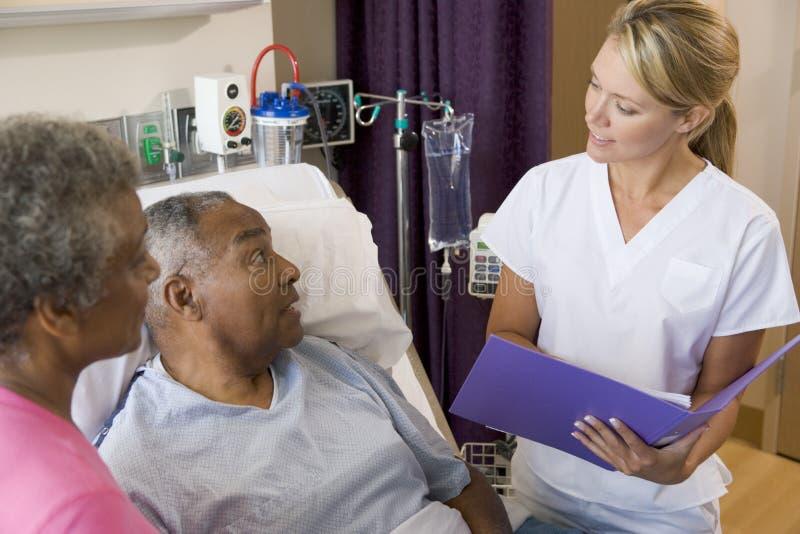 Doktor Talking To Senior Couples stockfoto