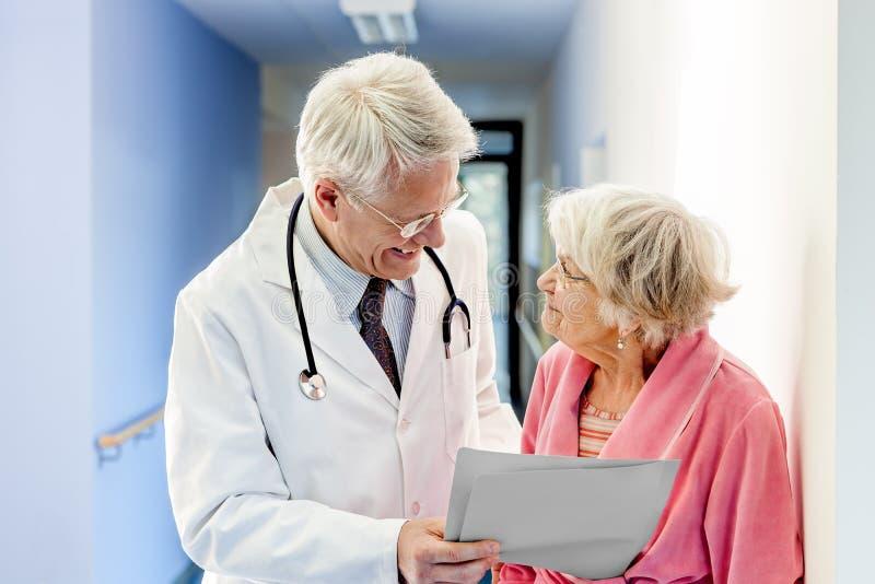 Doktor Talking zur alten Frau über gute Ergebnisse lizenzfreie stockfotografie