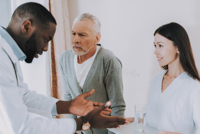 Doktor Tell Nurse über Heilung Älterer Mann hören lizenzfreie stockbilder