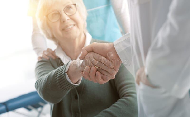 Doktor und älterer Patient, die Hände im Büro rütteln stockfoto