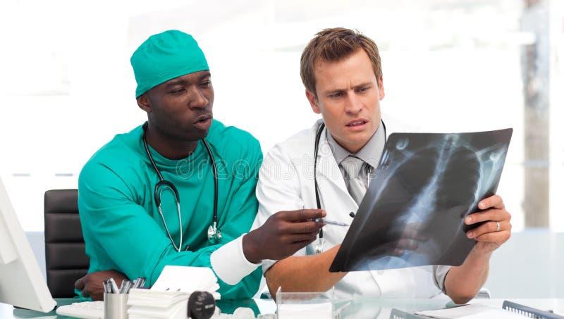 Doktor und Chirurg, die einen Röntgenstrahl betrachten lizenzfreie stockbilder