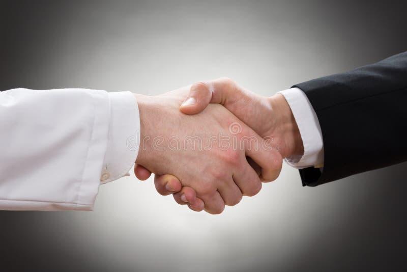 Doktor und Geschäftsmann, die Hand rütteln stockfoto