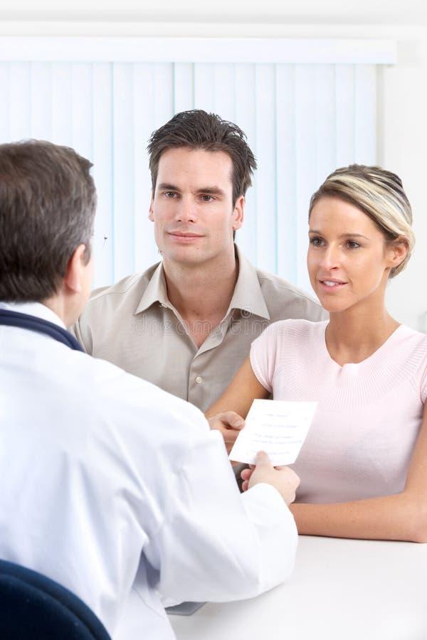 Doktor und junge Paare lizenzfreie stockfotos