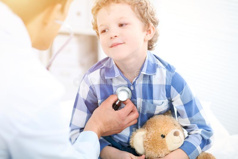Doktor- und Kinderpatient Arzt überprüft kleinen Jungen durch Stethoskop Medizin und Kinder` s Therapiekonzept lizenzfreie stockfotografie