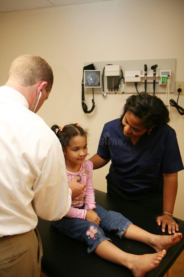 Doktor und Krankenschwester überprüfen jungen Patienten lizenzfreies stockbild