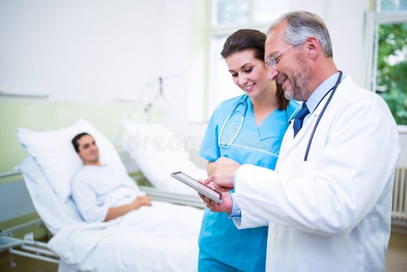 Doktor und Krankenschwester, die auf digitaler Tablette sich besprechen lizenzfreies stockfoto
