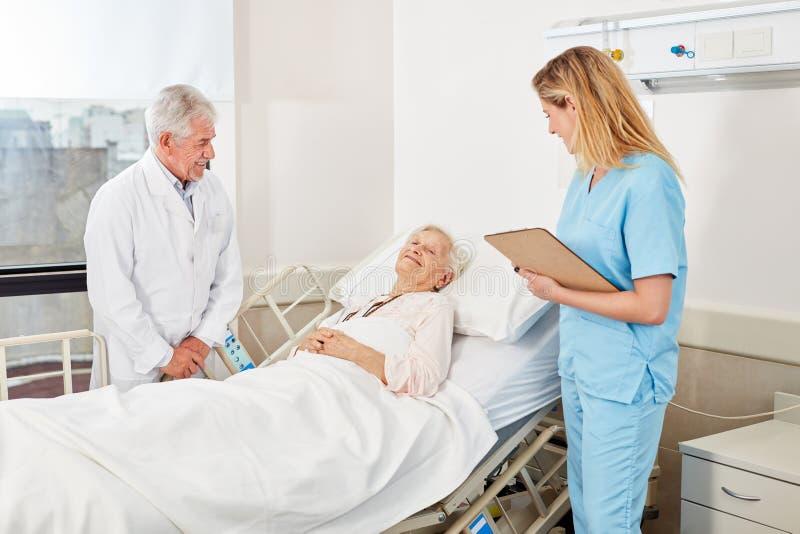 Doktor und Krankenschwester am Kopfende lizenzfreies stockbild