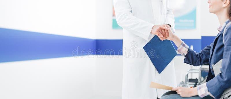 Doktor und Patient, die Hände rütteln stockfotos