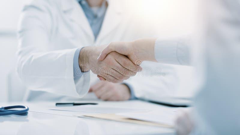 Doktor und Patient, die H?nde im B?ro r?tteln stockbilder