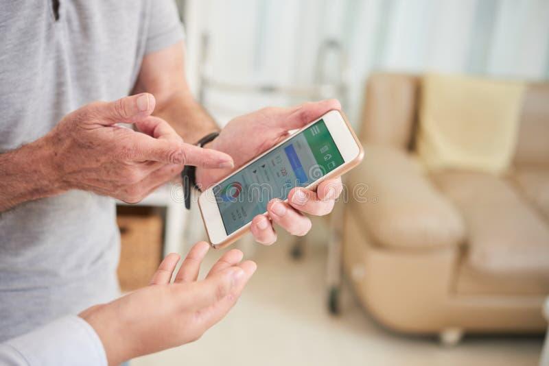 Doktor und Patient, die Heide App besprechen lizenzfreie stockbilder