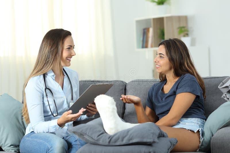 Doktor und Patient, die zu Hause sprechen stockfoto
