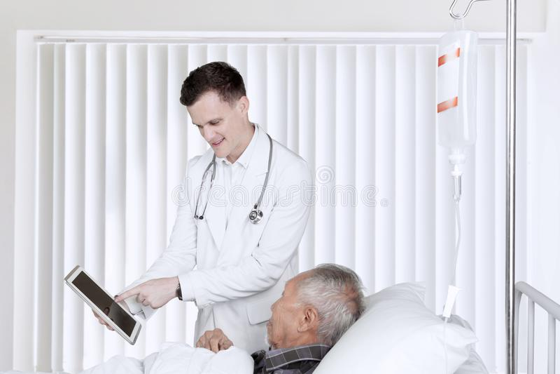 Doktor und Patient mit Tablette im Aufwachraum lizenzfreie stockfotos