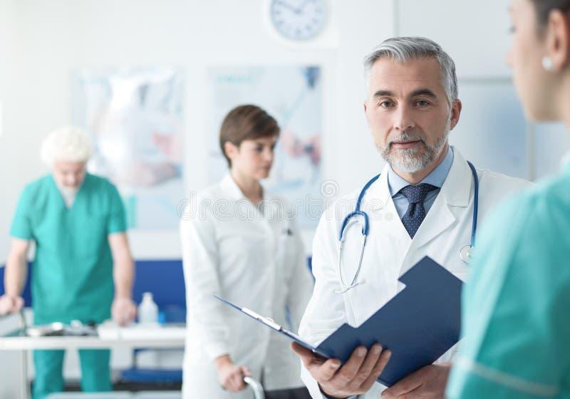 Doktor undersökande sjukdomshistorier för patient` ett s royaltyfria bilder