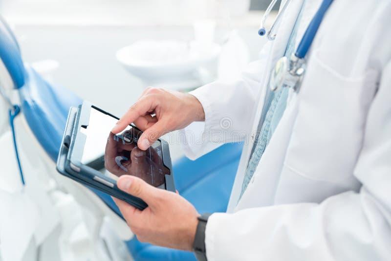 Doktor unter Verwendung des Tablet-Computers in seinem Büro lizenzfreies stockfoto