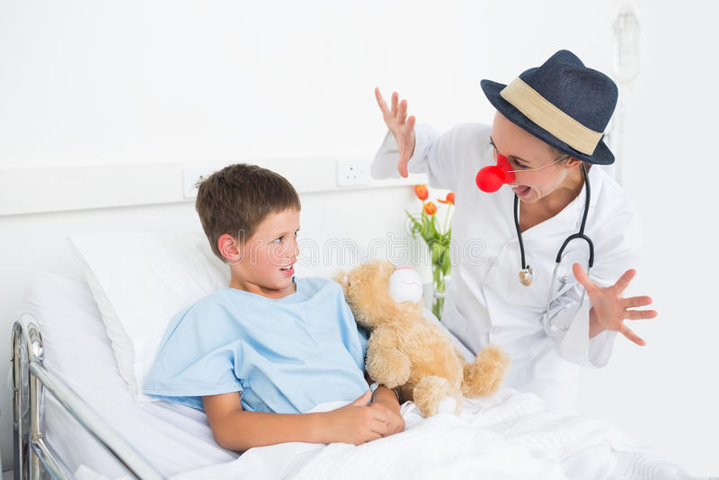 Doktor in unterhaltsamem krankem Jungen des Clownkostüms im Krankenhaus lizenzfreie stockbilder
