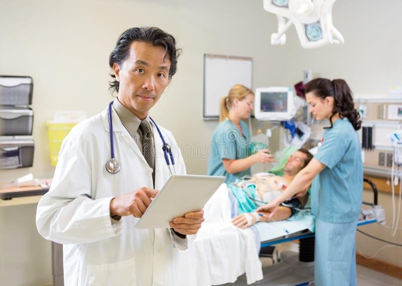 Doktor Using Digital Tablet während Krankenschwester-Behandlung stockfotos