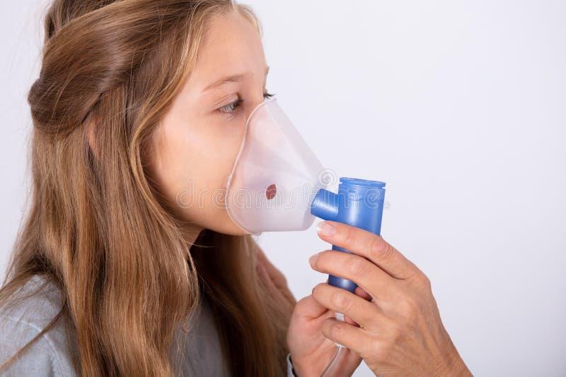 Doktor Using Inhaler Mask p? flicka arkivfoto