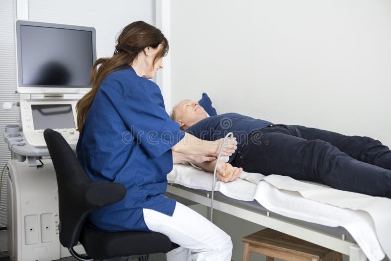 Doktor Using Ultrasound Probe på Male& x27; s-hand i sjukhus royaltyfri fotografi
