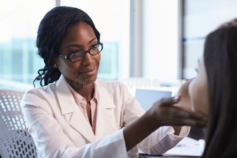 Doktor In White Coat som i regeringsställning undersöker den kvinnliga patienten royaltyfri bild