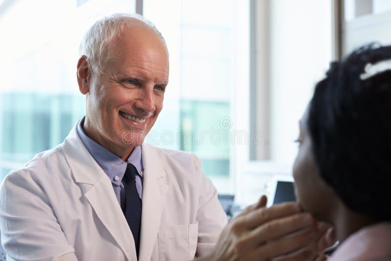Doktor In White Coat som i regeringsställning undersöker den kvinnliga patienten royaltyfri fotografi