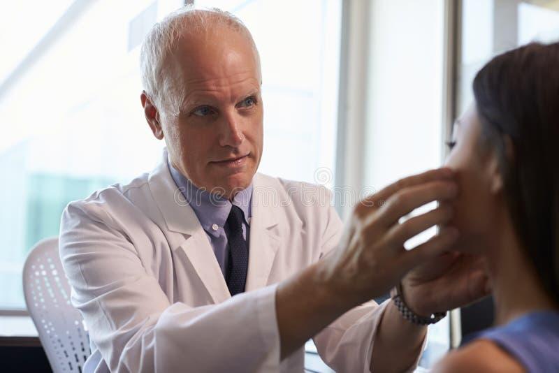 Doktor In White Coat som i regeringsställning undersöker den kvinnliga patienten arkivbilder