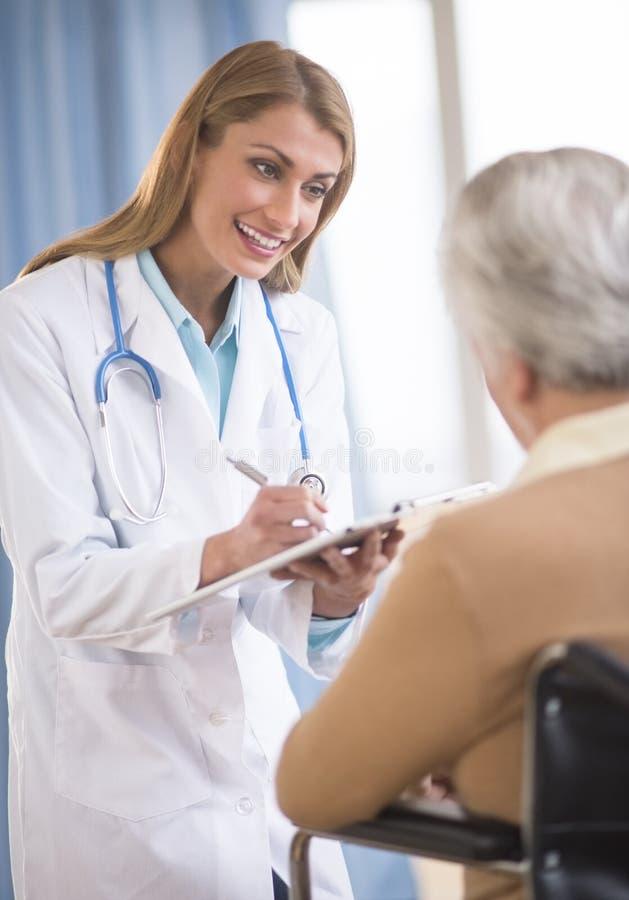 Doktor Writing On Clipboard, medan meddela med pensionären Woma royaltyfria bilder
