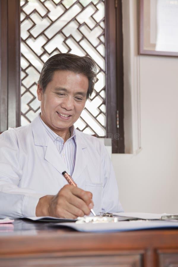 Doktor Writing på hans skrivbord arkivbilder