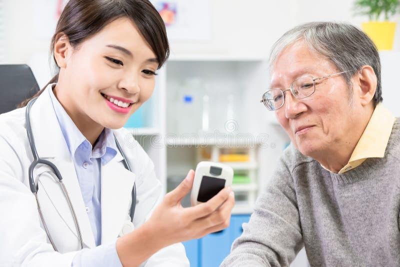 Doktor zeigen Blutzuckertest lizenzfreie stockfotos