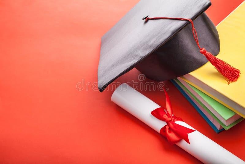 Doktorand- hatt och bok royaltyfri fotografi