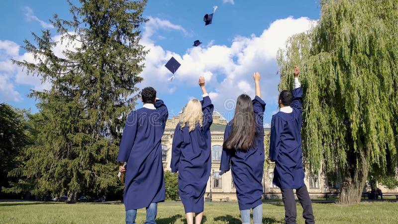 Doktorander som kastar upp fyrkantiga hattar, populär tradition, högre utbildning royaltyfri foto