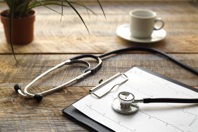 Doktorarbeitsplatz mit einem Stethoskop am Holztisch stockbilder