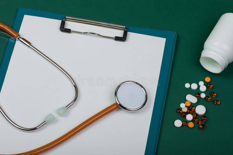 Doktorarbeitsplatz - orange Stethoskop, Pillen, medizinische Flaschen und leeres Klemmbrett auf Gr?nbuchhintergrund stockfotos