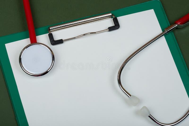 Doktorarbeitsplatz - rotes Stethoskop und leeres Klemmbrett auf Grün lizenzfreie stockfotografie