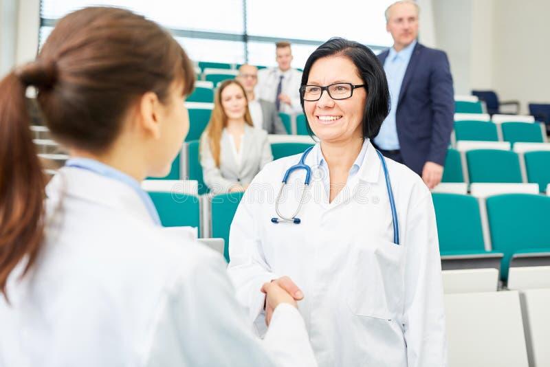 Doktoren beglückwünschen Frau mit Händedruck lizenzfreie stockfotos