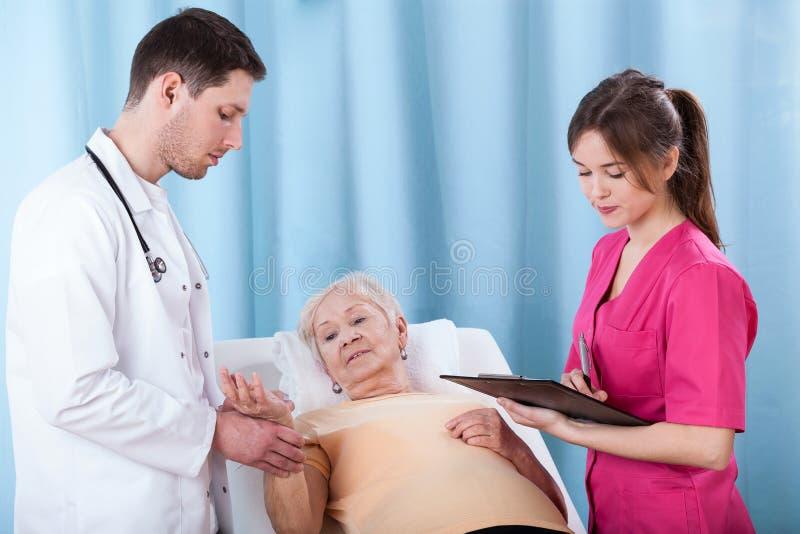 Doktoren, die ältere Frau bestimmen lizenzfreies stockbild
