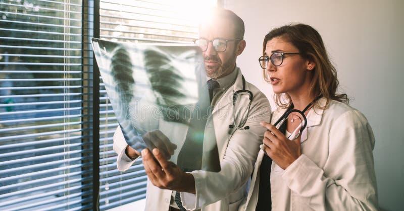 Doktoren, die geduldige Krankheit unter Verwendung des Röntgenstrahls bestimmen stockbild