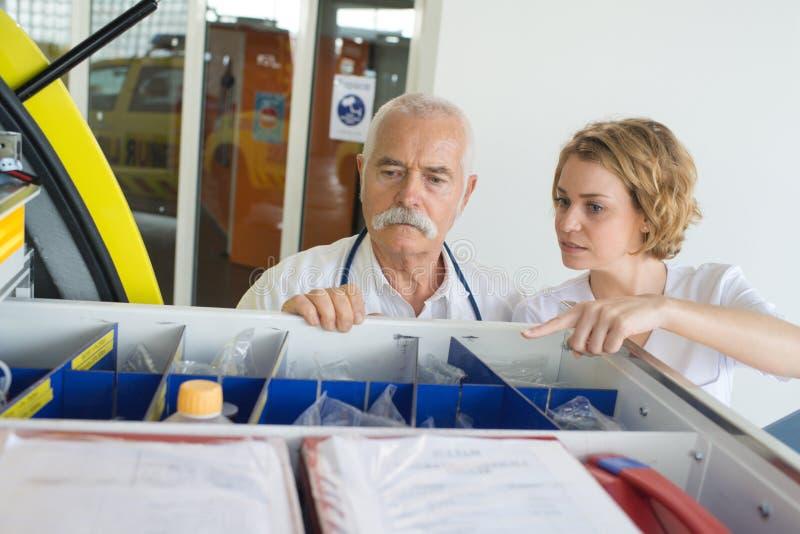 Doktoren, die Versorgungen im Notwarenkorb überprüfen stockfoto
