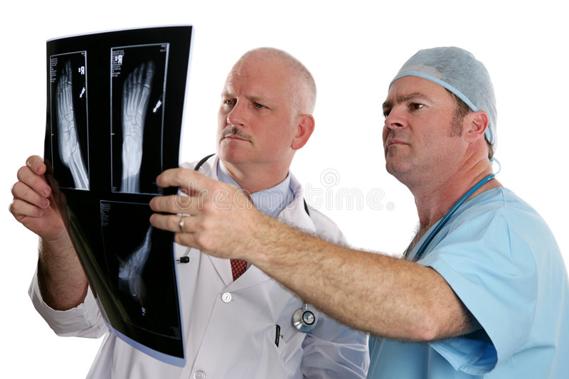 Doktoren Examining Xrays lizenzfreie stockfotos