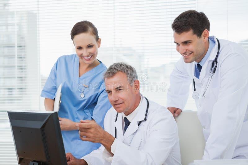 Doktoren und Chirurg, die zusammen an Computer arbeiten stockfotografie