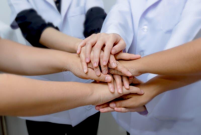 Doktoren und Krankenschwestern in einem Ärzteteam, das Hände stapelt stockbild