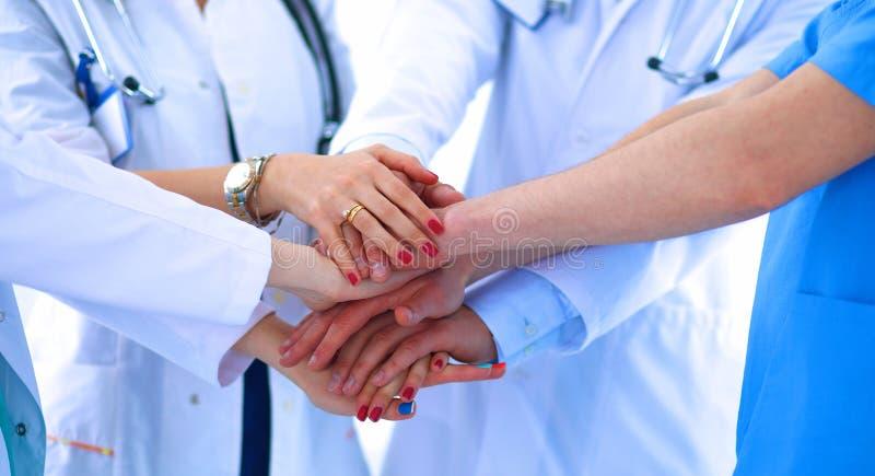 Doktoren und Krankenschwestern in einem Ärzteteam, das Hände stapelt stockfoto