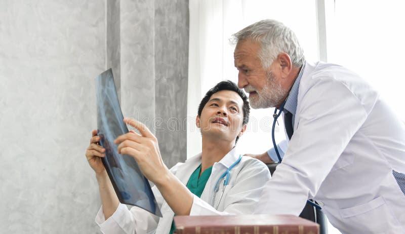 Doktorer för hög man för man och för barn undersöker asiatiska röntgenstrålefilmen royaltyfri fotografi