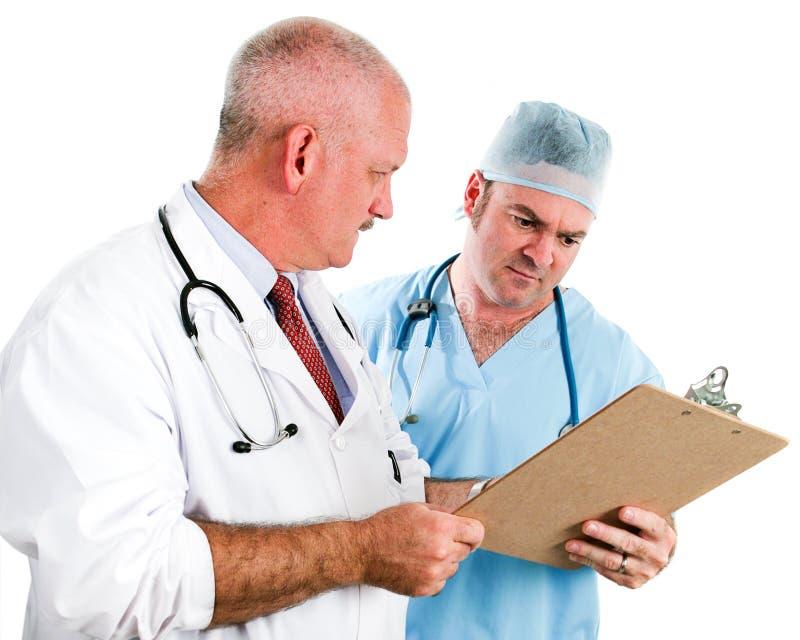 Doktorer granskar det tålmodiga diagrammet arkivbild