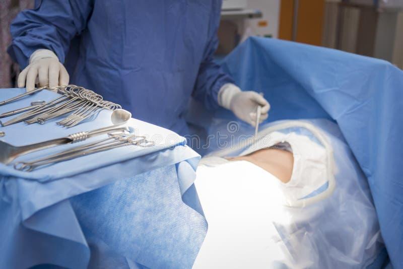 Doktorer med hj?lpmedel i h?nder som g?r kirurgi i operationrum H?lsov?rd och sjukhusbegrepp royaltyfri bild
