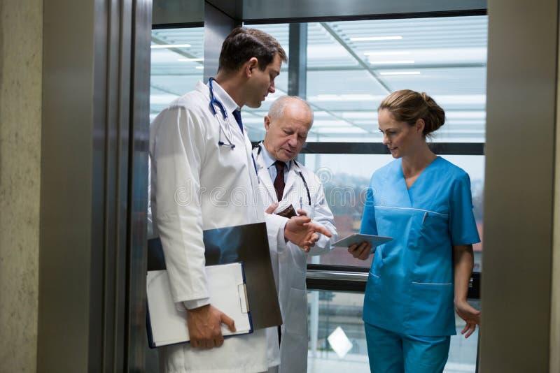 Doktorer och kirurg som använder den digitala minnestavlan i hiss royaltyfria foton
